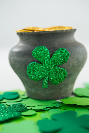 lucky charm: St. Patricks Day shamrock and pot filled with chocolate gold coins on white background