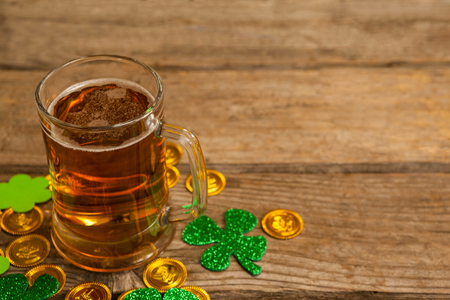 lucky charm: Mug of beer, chocolate gold coins and shamrock for St Patricks Day on wooden table