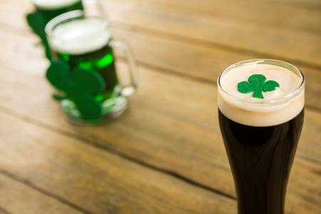 lucky charm: St Patricks Day glass of beer with shamrock on wooden surface Stock Photo