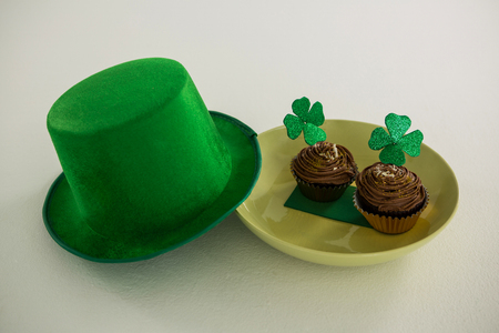 lucky charm: St Patricks Day leprechaun hat with shamrock on cupcake on white background Stock Photo