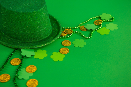 St. Patricks Day leprechaun hat, chocolate gold coins, beads and shamrocks on green background
