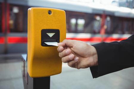 Hand of businessman punching ticket on platform