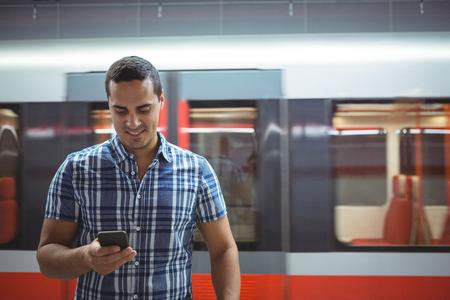 pone: Smiling executive using mobile phone on platform Stock Photo