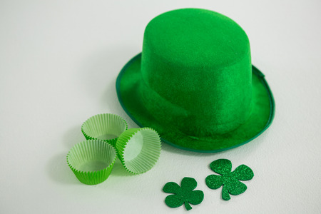 St Patricks Day leprechaun hat with shamrock and cup cake case on white background