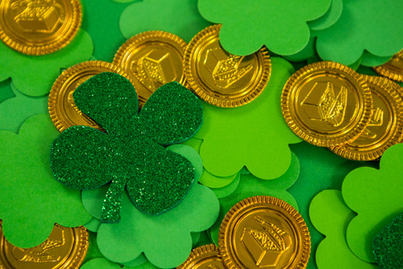 St Patricks Day shamrocks and gold chocolate coin on green background