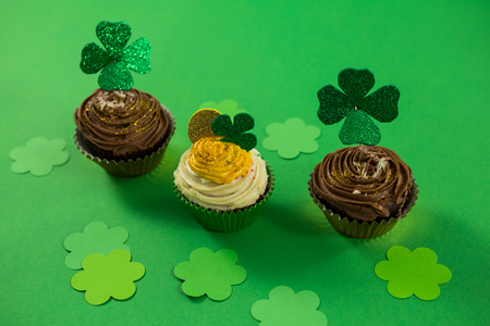 lucky charm: St Patricks Day shamrock on the cupcake on green background