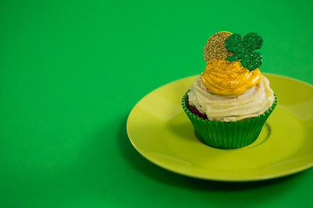 St Patricks Day shamrock on the cupcake kept in plate on green background Stock Photo