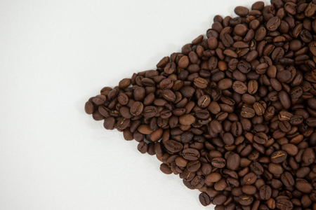 Roasted coffee beans arranged on white background