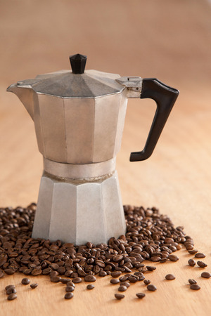 Metallic coffee maker with coffee beans on wooden background