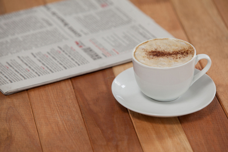 Close-up of black coffee and newspaper on wooden background Stock Photo