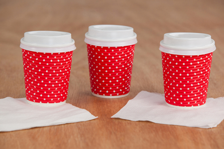 Three disposable coffee cup with tissue paper on wooden background