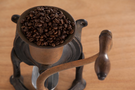 Vintage coffee grinder with coffee beans on wooden background Stock Photo