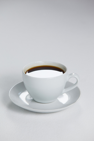 Black coffee served in white cup on white background Stock Photo