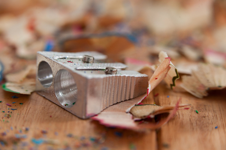 Sharpener and various colored pencil shavings on wooden background Stock Photo