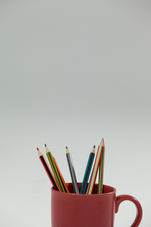 Colored pencils kept in cup on white background
