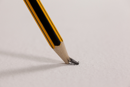 Close-up of broken pencil on white background
