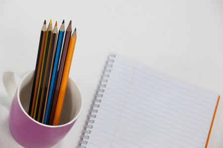 Colored pencils kept in cup and notepad on white background Stock Photo
