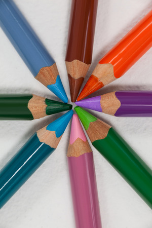 Close-up of colored pencils arranged in a circle on white background