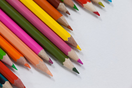 Close-up of colored pencils arranged in a wave pattern on white background
