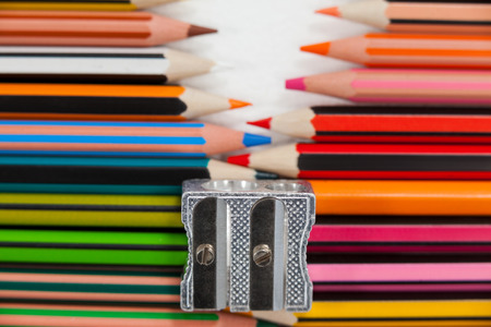 Close-up of colored pencils and sharpener on white background