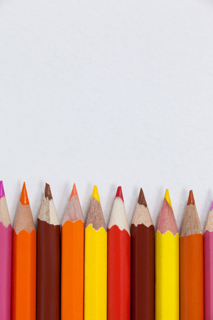 Close-up of colored pencils arranged in a row on white background Stock Photo