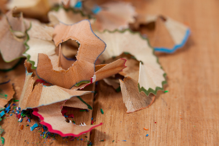 Shavings of various colored pencil on wooden background Stock Photo