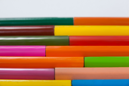 Close-up of colored pencils arranged in interlock pattern on white background