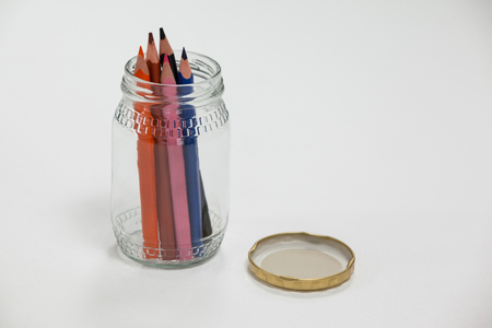 Colored pencils kept in a glass jar on white background