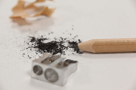 Close-up of sharpener and pencil on white background