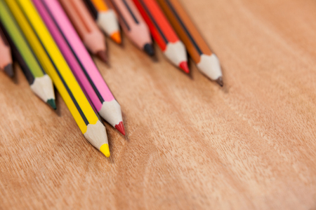 Close-up of colored pencils arranged in a wave pattern on wooden background
