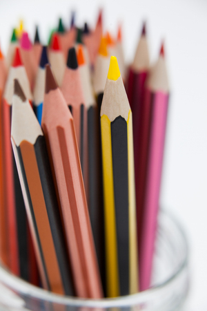 Close-up of colored pencils kept in a glass jar on white background