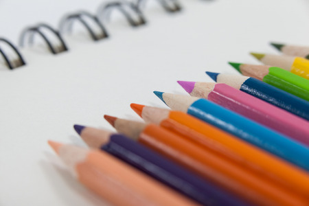 Close-up of colored pencils and notebook on white background Stock Photo