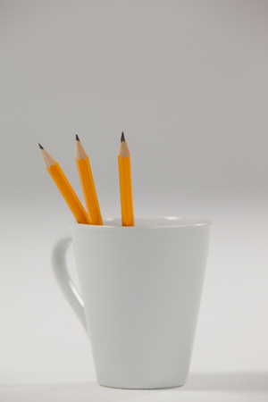 Three pencils kept in cup on white background