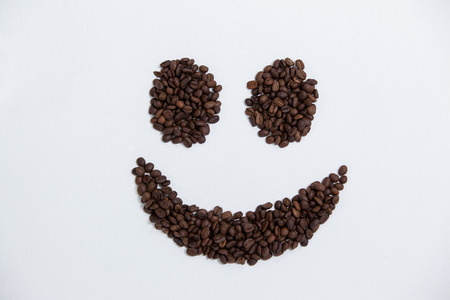 Coffee beans forming smiley on white background