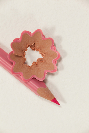 Close-up of pink colored pencil with shavings on white background