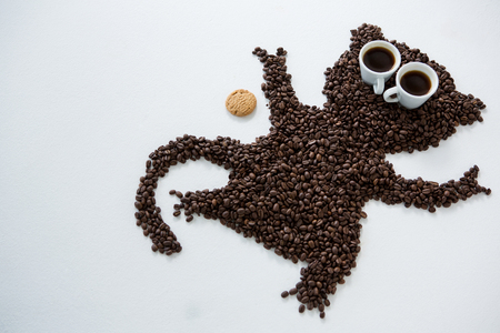 Coffee beans forming monkey shape on white background