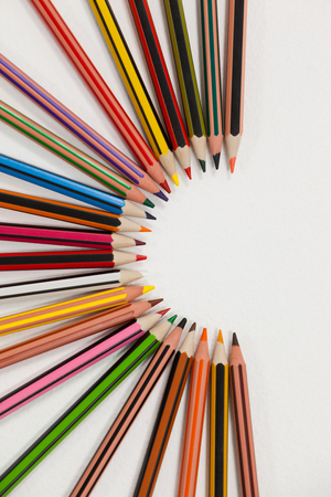 Colored pencils arranged in a semi-circle on white background
