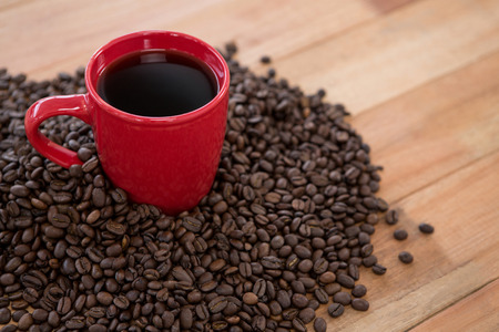 Close-up of coffee with coffee beans on wooden table Stock Photo