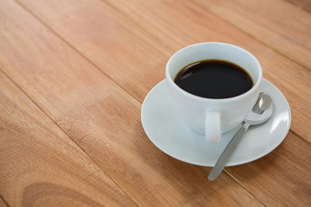 Black coffee served in white cup on wooden table
