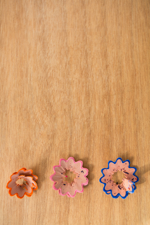 Colored pencil shavings in a flower shape on wooden background Stock Photo