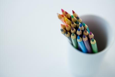 Colored pencils kept in mug on white background Stock Photo