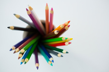Close-up of colored pencils kept in mug on white background Stock Photo