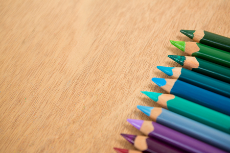 Colored pencils arranged in a row on wooden background Stock Photo