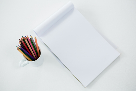 Colored pencils kept in mug with notepad on white background Stock Photo