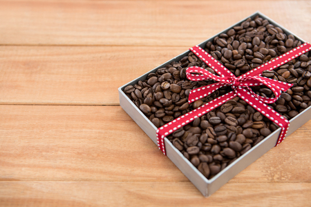 Roasted coffee beans in gift box on wooden background