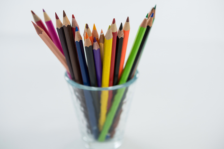 Close-up of colored pencils kept in glass on white background Stock Photo