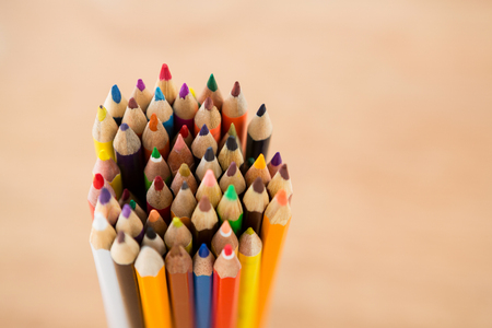 Close-up of bunch of colored pencil on beige background