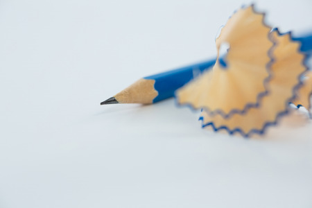 Close-up of blue pencils shavings with pencils on white background