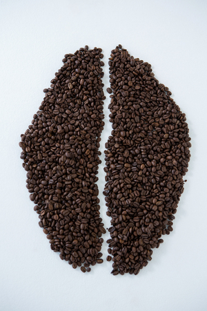 Coffee beans forming coffee bean shape on white background Stock Photo