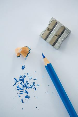 Close-up of red color pencil with pencil shaving and sharpener on white background